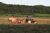 Modern day tractor pulling combine in oats field