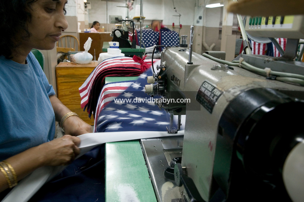 21 June 2005 - Oaks, PA - Idegonda Mauras sows American flags together at the Annin & Co. flag manufacturing plant in Oaks, PA.