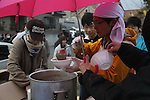 March 30, 2011, Ishinomaki, Miyagi, Japan - More than two weeks after the tsunami, volunteer groups look to contribute to the relief effort. Peaceboat volunteers make hot meals at the camp on the grounds of Senshu University and then distribute them around the city. The residents of the Shirasagidai neighborhood wait in line for curry udon. (Photo by Wesley Cheek/AFLO) [3682].