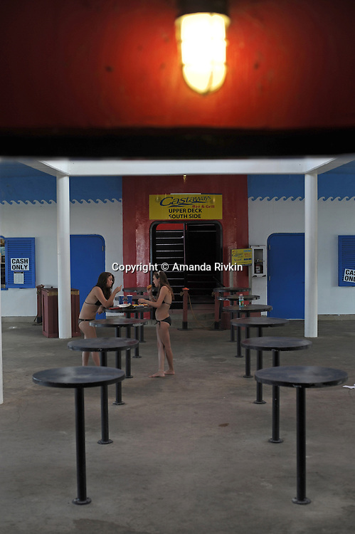 Girls in bikinis eat snacks on the lower deck of Castaways at the North Avenue beach in Chicago, Illinois on August 18, 2008.