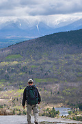 A hiker explores the rocky summit of Middle Sugarloaf Mountain during the spring months. The Presidential Range can be seen in the background.  Located in Bethlehem, New Hampshire USA