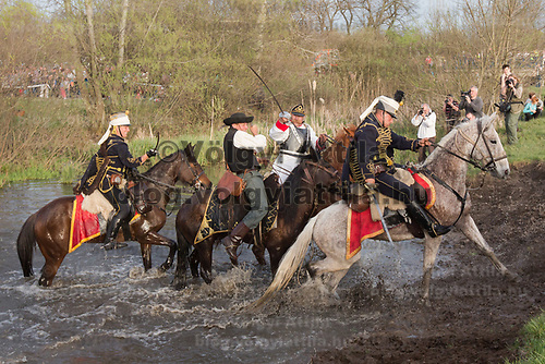 People in period military uniforms cross a creek as they re-enact a historic battle in Tapiobicske (some 70 km East from Budapest), Hungary on April 04, 2016. ATTILA VOLGYI