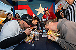WATERBURY, CT. 12 January 2020-011220BS16 - From left, Baked Potato contestants Jose Rivera, Evan Scarzella, and Steve Shircliff dig in eating their baked potatoes, during a baked potato eating contest at the Little Puerto Rico Restaurant in Waterbury on Sunday. The person who ate the whole potato, skin and all, the fastest, won $50 and a championship belt. Bill Shettle Republican-American