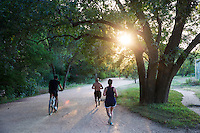 Shot of local people jogging, running and bicycling to maintain a fit healthy lifestyle along the Lady Bird Lake Hike and Bike Trail - stock image.