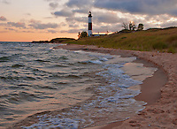 Big Sable Light sits stoickly against a morning sky at sunrise on the eastern Lake Michigan shore in Ludington County, Michigan