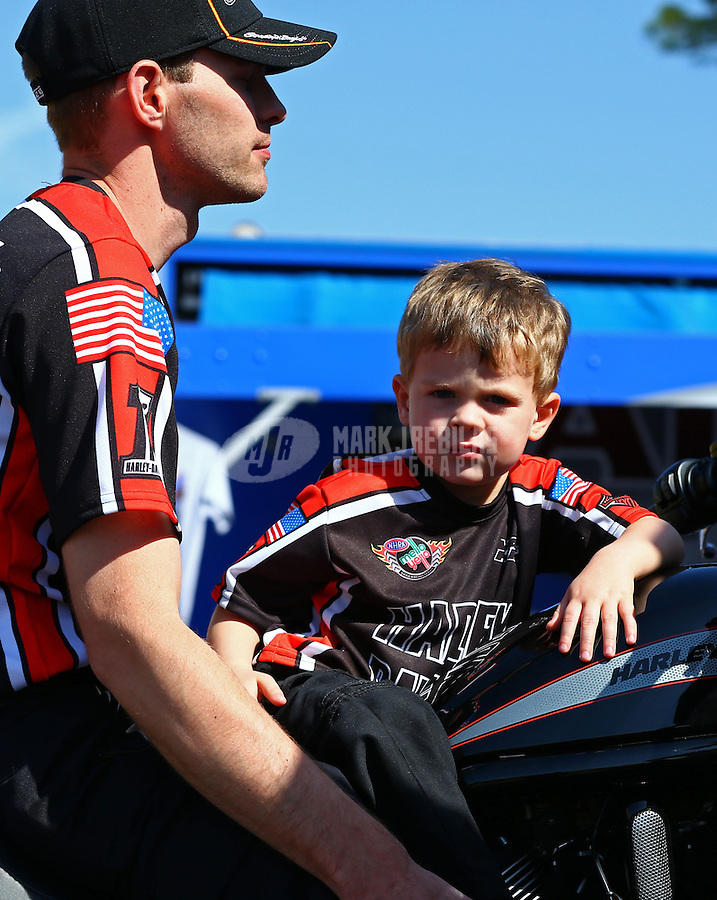 Mar 15, 2014; Gainesville, FL, USA; Declan Hines , son of NHRA pro stock motorcycle rider Andrew Hines lays on his dads motorcycle in the pits during qualifying for the Gatornationals at Gainesville Raceway Mandatory Credit: Mark J. Rebilas-USA TODAY Sports