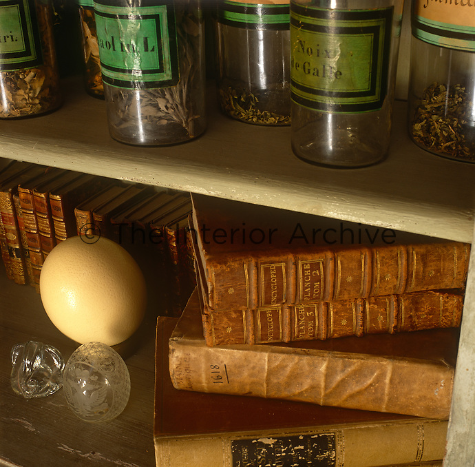 Glass jars with dried herbs and books with red covers are displayed oon shelves.