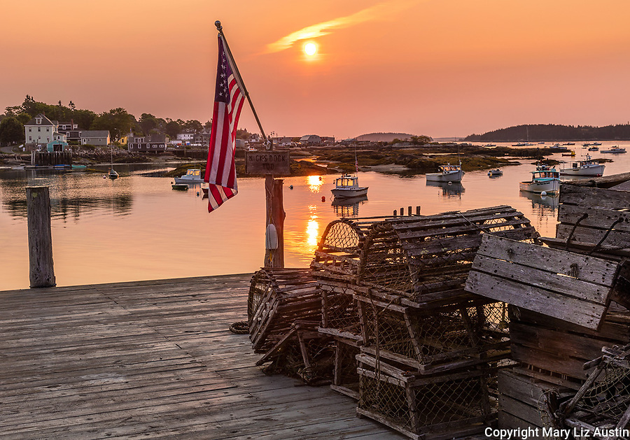 Stonington, ME: American flag illuminated by sunrise on dock with wooden lobster traps overlooking Stonington Harbor