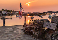 Stonington, ME: American flag illuminated by sunrise on dock with wooden lobster traps overlooking Stonington Harbor