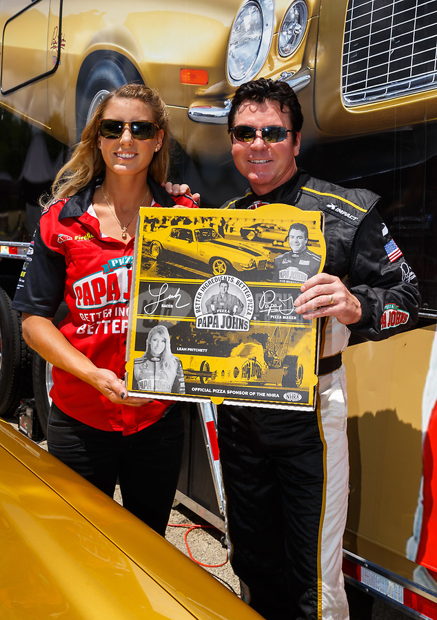Jul 8, 2017; Joliet, IL, USA; NHRA top fuel driver Leah Pritchett (left) and Papa Johns Pizza founder John Schnatter show off the newly released NHRA themed extra large pizza box during qualifying for the Route 66 Nationals at Route 66 Raceway. Mandatory Credit: Mark J. Rebilas-USA TODAY Sports