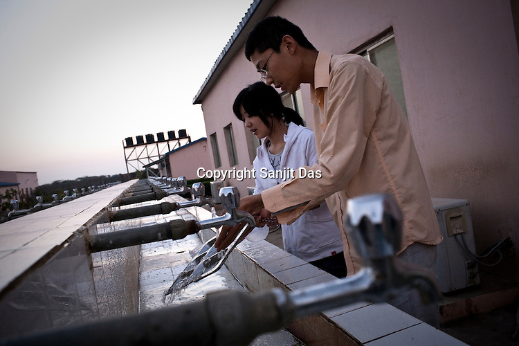 25 year old Chinese interpreter, Yuan Lei helps his girlfriend, Cui Yan (left) with dishwashing after breakfast at the Chinese Colony in the Adani Power plant in Mundra port industrial city of Gujarat, India. Indian power companies have handed out dozens of major contracts to Chinese firms since 2008. Adani Power Ltd have built elaborate Chinatowns to accommodate Chinese workers, complete with Chinese chefs, ping pong tables and Chinese television. Chinese companies now supply equipment for about 25% of the 80,000 megawatts in new capacity.