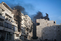 In this Wednesday, Dec. 05, 2012 photo, smoke rises from residential buildings in fire as they are shelled by mortar and tank artillery during heavy fighting between rebels and the Syrian army in Aleppo, Syria. (AP Photo/Narciso Contreras)