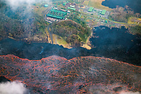 lava originating from fissure 8 in the east rift zone of Kilauea Volcano, flows as a river of lava past Puna Geothermal Ventrures, a geothermal electricity plant in Puna, Big Island, Hawaii, USA