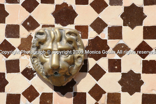 A lion head fountain in a brown and white tiled patio in Marrakesh, Morocco.