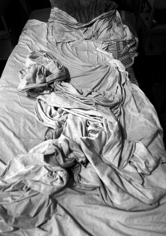 Dirty sheets lay crumpled on a patient's bed in the psychiatry ward of a county hospital in Bulgaria on August 23, 2007.
