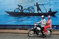 A happy couple on their scooter in the streets of Phnom Penh in front of a large street mural depicting fisherman. Street scene in Phnom Penh, Cambodia