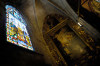 Religious painting and stained glass window inside a chapel at the Seville Cathedral, Seville, Andalusia, Spain.