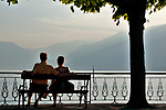 A couple enjoys the view of Lake Como, Italy while sitting on a bench in Bellagio at sunset
