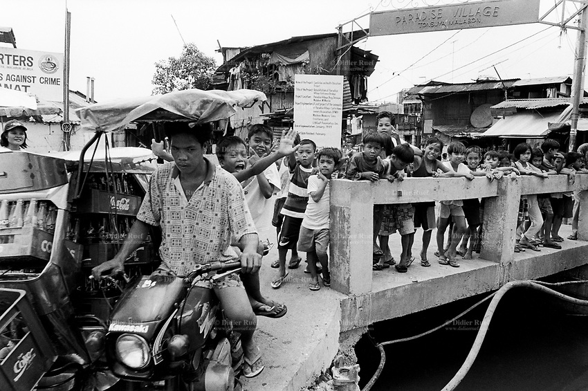 Philippines. National Capital Region. Manila. A group of children stands on the newly built bridge built by the non-governmental organization (NGO) Médecins Sans Frontières (MSF) Switzerland in order to improve the living conditions and the health situation. A man rides a Kawasaki sidecar and transports empty Coca Cola bottles in boxes. Paradise village has a population of 15'000 people and is a part of Barangay Tonsuya situated on Lettre Road in Malabon. Manila is part of the National Capital Region (NCR) on Luzon island. Manila is the capital of the Philippines and one of the sixteen cities that comprise Metro Manila. Metro Manila is the most populous metropolitan area in the Philippines. © 1999 Didier Ruef