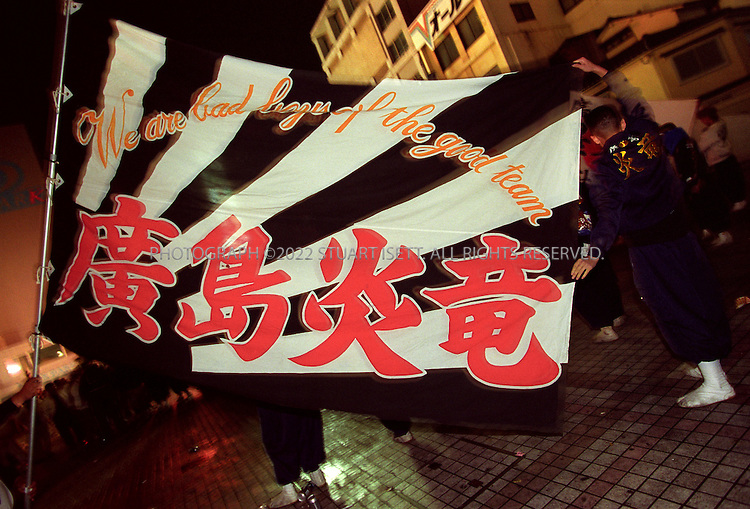 11/18/1999--Hiroshima, Japan..Bosozoku gang member hold up a gang flag after a night of rioting on the streets of Hiroshima. Such gangs have been common in Japan for many years and are considered stepping stones to join yakuza gangs and 'uyoku' or rightwing nationalsist groups....All photographs ©2003 Stuart Isett.All rights reserved.This image may not be reproduced without expressed written permission from Stuart Isett.