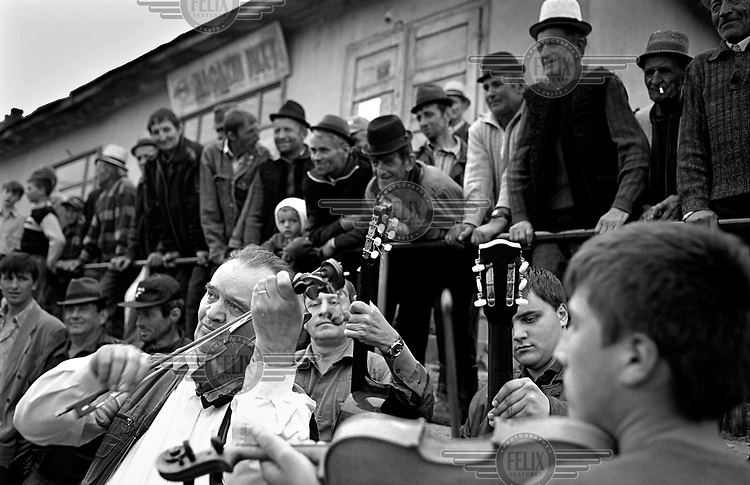 A band plays music to an audience at a wedding party in Maramures.