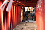 A man praying at the end of a row of torii at a small local shrine in Imaike, Nagoya