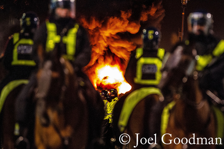 © Joel Goodman - 07973 332324 . 09/12/2010 . London , UK . Four mounted police officers separate crowds from a bellowing fire , set on Parliament Square . Students and their supporters clash with mounted police during a demonstration in Parliament Square in London against government cuts to student support , Educational Maintenance Allowance ( EMA ) and rising university tuition fees . Photo credit : Joel Goodman
