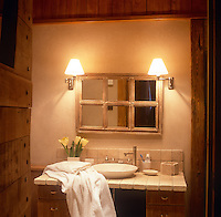 A view into a rustic style bathroom. Two wall lights are placed on either side of a mirror above a washbasin set on a stone topped drawer unit.