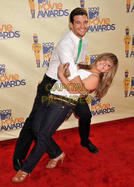 MARK BALLAS & SHAWN JOHNSON.18th Annual MTV Movie Awards - Arrivals held at the Universal Gibson Amphitheater, Universal City, CA, USA..May 31st, 2009.full length shirt green tie trousers white top black jeans denim brown sandals dancing bending leaning gesture .CAP/ADM/BP.©Byron Purvis/AdMedia/Capital Pictures.