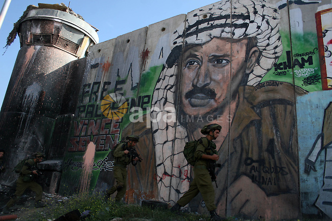 """Israeli soldier walk past murals painted on the controversial Israeli separation barrier during clashes with Palestinian stone throwers at the Israeli manned Qalandia checkpoint between Jerusalem and the West Bank city if Ramallah on May 14, 2011, as Palestinians gather in the run up to tomorrow's 63rd anniversary of the 1948 creation of Israel, an event known to Arabs as the """"nakba"""" or """"catastrophe. Photo by Issam Rimawi"""