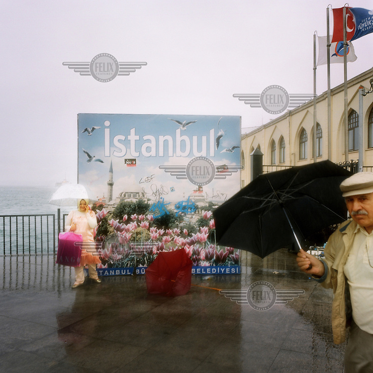 People shield themselves from the wind and rain with umbrellas as they walk past an advertisement for Istanbul at the Kadikoy ferry station.