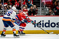 WASHINGTON, DC - JANUARY 31: Richard Panik #14 of the Washington Capitals  makes a pass as Johnny Boychuk #55 of the New York Islanders closes in during a game between New York Islanders and Washington Capitals at Capital One Arena on January 31, 2020 in Washington, DC.