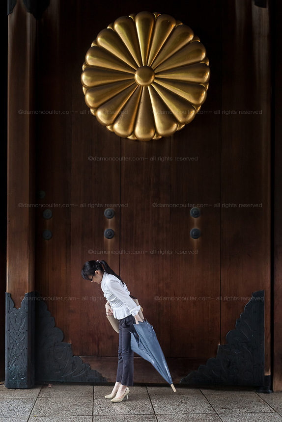 A Japanese woman bows as she enters the shrine under gate with the Imperial Chrysanthemum crest on the door as Yasukuni shrine marks the 72nd anniversary of the end of the Pacific War. Yasukuni Shrine, Kudanshita, Tokyo Japan. Tuesday August 15th 2017. Nominally a event to honour Japan's war dead and call for continued peace, this annual gathering  at Tokyo's controversial Yasukuni  Shine also allows many Japanese nationalists to display their nostalgia for their Imperial past.Rightwing paramilitary groups, Imperial cos-players, politicians and many ordinary citizens come together at the shrine to march and wave flags. The day goes almost unreported in the mainstream Japanese media.