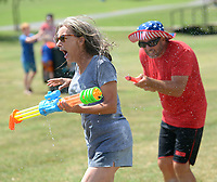 NWA Democrat-Gazette/ANDY SHUPE<br /> Melanie Houston (left) of Lowell laughs Wednesday, July 4, 2018, as she is sprayed with water by Mike Whitehead of Lowell, director and founder of Project Red Friday, during the second Fourth of July Water Balloon War organized by Project Red Friday at Ward Nail Park in Lowell. The organization works to raise awareness for military service members and their families by encouraging people to wear red on Fridays.