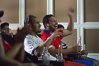 Denver, CO - Wednesday, June 18, 2014:  Chile fans (left to right) Jose Lopez and Diego Perez cheer on their team playing Spain in a World Cup first round match in Thornton, CO.  They were among two dozen Chileans who gathered to watch the match at a private screening room in a condominium complex in suburban Denver.