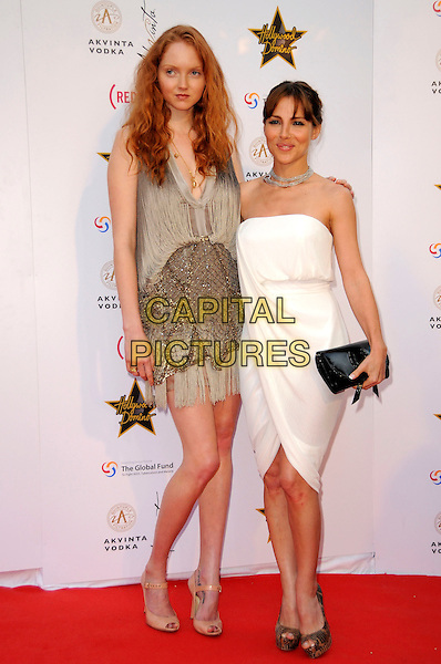 LILY COLE & ELSA PATAKY.The Akvinta Presents A Night of Hollywood Domino Party at The House at Cannes during the 62nd International Cannes Film Festival, Cannes, France..May 18th, 2009 .full length white strapless dress black clutch bag gold beige tassels .CAP/CAS.©Bob Cass/Capital Pictures.