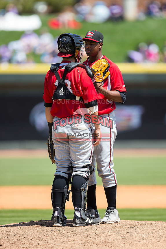 Carolina Mudcats catcher Joseph Odom (13) has a meeting on the mound with relief pitcher Mauricio Cabrera (22) during the game against the Winston-Salem Dash at BB&T Ballpark on April 22, 2015 in Winston-Salem, North Carolina.  The Dash defeated the Mudcats 4-2..  (Brian Westerholt/Four Seam Images)