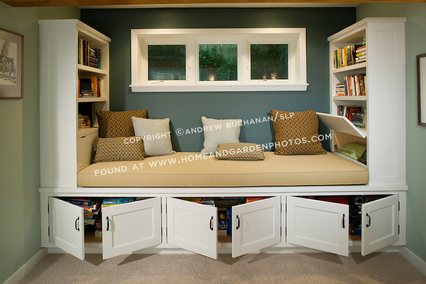 A roomy window seat bench offers a cozy space for reading, while the built-in bookshelves and cupboards surrounding it provide ample storage in this newly-remodeled basement. This image is available through an alternate architectural stock image agency, Collinstock located here: http://www.collinstock.com