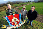 Kilgarvan GAA Club Chairman Tom Randles  and  fellow officers Jerh Lyne and Thomas O'Reilly at the Kilgarvan GAA Club field with the club crest that features St. Patrick's Church . In background on left is part of the adjoining  Presbytery site . Picture: Eamonn Keogh (MacMonagle, Killarney)