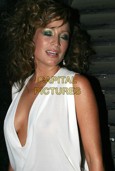 "REBECCA LOOS.Attends ""Christmas in July"" Fashion Show and Party, Pangaea, London,.13th July 2004..half length low cut white top green eye shadow make up gold bronzed skin eyes closed.Ref: AH.www.capitalpictures.com.sales@capitalpictures.com.©Capital Pictures."