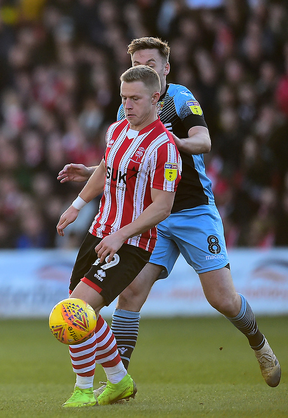 Lincoln City's Danny Rowe shields the ball from Stevenage's Joel Byrom<br /> <br /> Photographer Andrew Vaughan/CameraSport<br /> <br /> The EFL Sky Bet League Two - Lincoln City v Stevenage - Saturday 16th February 2019 - Sincil Bank - Lincoln<br /> <br /> World Copyright © 2019 CameraSport. All rights reserved. 43 Linden Ave. Countesthorpe. Leicester. England. LE8 5PG - Tel: +44 (0) 116 277 4147 - admin@camerasport.com - www.camerasport.com
