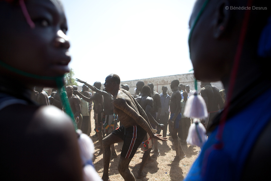 18 december 2010 - Juba, Southern Sudan - Members of the Mundari tribe from Central Equatoria State dance before the final of South Sudan's first commercial wrestling league between their tribe and the Dinka wrestlers from Bor, Jonglei State at Juba Stadium. The matches attracted large numbers of spectators who sang, played drums and danced in support of their favorite wrestlers. The match organizers hoped that the traditional sport would bring together South Sudan's many different tribes. Photo credit: Benedicte Desrus