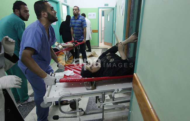 Palestinian medics treat a woman, whom medics said was wounded in an Israeli air strike, at a hospital in Rafah in the southern Gaza Strip August 4, 2014. A brief Israeli truce to allow aid to reach Palestinians ended on Monday amid accusations of strikes by both sides, while Jerusalem was rocked by two attacks that appeared to be a backlash against the war in Gaza. Gaza officials say 1,831 Palestinians, most of them civilians, have been killed and more than a quarter of the impoverished enclave's 1.8 million residents displaced. As many as 3,000 Palestinian homes have been destroyed or damaged. Israel has lost 64 soldiers in combat and three civilians to Palestinian cross-border rocket and mortar fire that has emptied many of its southern villages. Iron Dome interceptors, air raid sirens and public shelters have helped stem Israeli casualties. Photo by Ashraf Amra