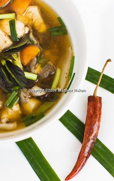 Tom Som Kai — Sour chicken soup with lemongrass and acacia leaves; Lao cuisine menu soup at  Restaurant Les 3 Nagas. Luang Prabang, Laos.