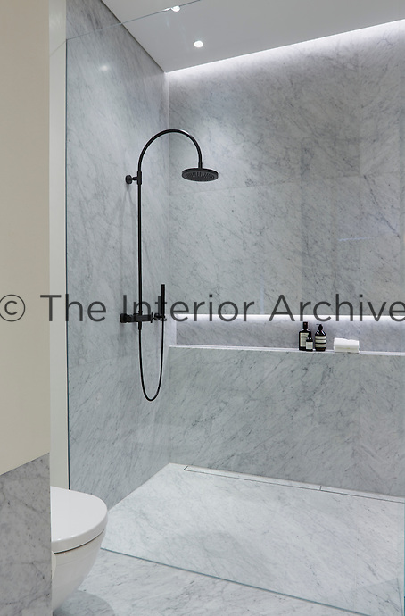 The en suite bathroom is cool and stylish in grey marble with a walk-in shower.