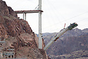 Colorado River Bridge construction (Arizona side). Traffic currently travels on a two lane road over Hoover Dam which causes traffic congested and poses a security risk. Large trucks are not allowed over the dam and must make a major detour around the area. To deal with these problems the US 93 Highway, Hoover Dam Bypass project was developed approximately 1,500 feet downstream of the dam. It consists of 3.5 miles of roadway, two lanes in each direction, with a 1,900 foot long twin-rib concrete arch bridge 880 feet above the Colorado River's Black Canyon. It will be the longest concrete arch in the US and the 5th longest in the world. It will involve 60,000 cubic yards of concrete, 8,000 tons of steel, over 3.5 million cubic yards of earthwork excavation/embankment, and cost approximately $240 million.* Construction began in 2005 and is expected to be completed in 2010. US 93 is on the North American Free Trade Agreement (NAFTA) route between Mexico and Canada, and it is also the major commercial route between the states of Arizona, Nevada, and Utah. Photo taken February 2009..*Statistics source: Central Federal Lands Highway Division of the U.S. Department of Transportation's Federal Highway Administration, the lead managers of the project.