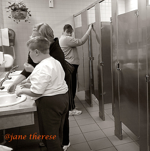 A woman watches as Jill washes Drew's hands after he uses the toilet in the woman's bathroom. Drew at age 10, is old enough to use the men's bathroom, but because he is severely autisitc and needs constant care, that option is not a choice. Photo by Jane Therese