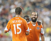 Houston Dynamo midfielder Adam Moffat (16) celebrates his goal with teammates.  In a Major League Soccer (MLS) match, Houston Dynamo (orange) defeated the New England Revolution (blue), 2-1, at Gillette Stadium on July 13, 2013.
