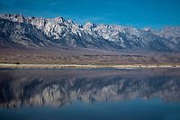 The Sierra Nevada Mountins are reflected in the waters of Owens Lake at Owens Valley, California