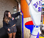 "Junior Francesca Vitale works with Brother Mark Elder, C.M., an adjunct faculty member in DePaul's art, media and design program, Saturday, July 28, 2018, as they team with other present and former students to install the first of three new murals under the Fullerton ""L"" Station in Lincoln Park. The caricature of DePaul basketball star George Mikan, a 1959 Naismith Memorial Basketball Hall of Fame inductee, was installed on a pillar directly under the CTA's Brown and Purple Line. Later in the day, the group installed a mural featuring a montage of historical images highlighting the 50th anniversary of DePaul's Black Student Union, then one around a column celebrating the opening of the university's Loop Campus.<br /> <br /> Elder's artistic retrospective, titled ""The Story of 'The Little School Under the 'L'', will eventually feature 25 murals permanently installed on the massive concrete pillars that support the ""L"" station nearest the university's Lincoln Park Campus. (DePaul University/Jamie Moncrief)"